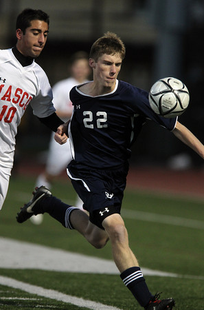 St. John's Prep senior Matthew Brady, right, tries to control the ball while being held by Masco senior Keyon Olia, left, during the second half of play. David Le/Staff Photo