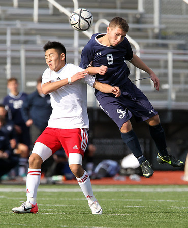 St. John's Prep senior striker Levon Kazelyn, right, leaps in the air to win a header over Somerville junior Elliot Rippe, left, during the second half of the Eagles' 1-0 loss in the D1 North Final on Sunday afternoon. David Le/Staff Photo