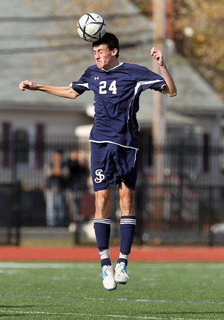 St. John's Prep junior defense Cory Lang leaps high in the air to win control of a header against Somerville in the D1 North Final on Sunday afternoon at Manning Field in Lynn. David Le/Staff Photo