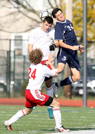 St. John's Prep junior defense Cory Lang, right, leaps high in the air to win a head ball from Somerville senior Felix DeBona, center, while Somerville's Marcelo Brociner, left, looks on. The Eagles fell to the Highlanders 1-0 in the D1 North Final match at Manning Field in Lynn on Sunday afternoon. David Le/Staff Photo