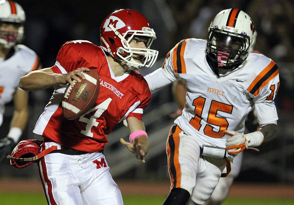 Masconomet senior quarterback Chris Schleer, left, looks to pass while being chased down by Beverly junior Sam Mulumba, right, on Friday evening. David Le/Staff Photo