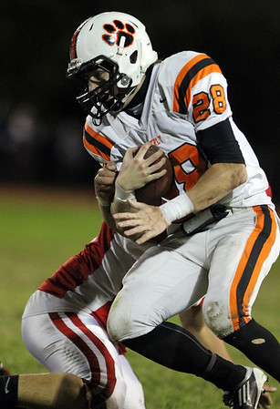 Beverly senior Kenny Pierce holds onto the ball while being hit by a Masconomet defender on Friday evening. David Le/Staff Photo