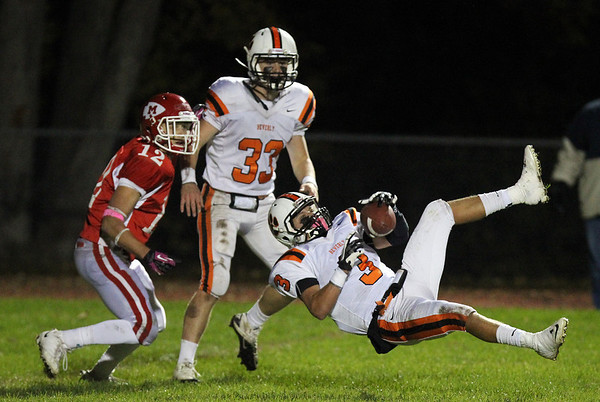 Beverly senior defensive back Ryan Shipp, right, comes down with the football after making a leaping intereption on Masco quarterback Chris Schleer, as Masco's Corey Tines, left, and Beverly's Brendan Flaherty, center, look on. David Le/Staff Photo