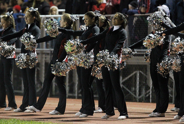 Masconomet cheerleaders scream out encouragement for their team during Friday evening's game against Beverly. David Le/Staff Photo