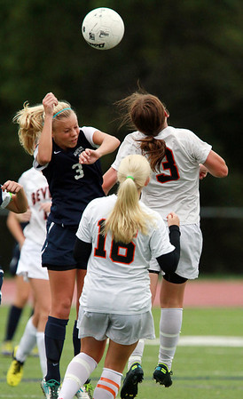 Swampscott's Catt Singley, left, and Beverly's Casey Cook, right, battle for a head ball on Thursday afternoon. David Le/Staff Photo