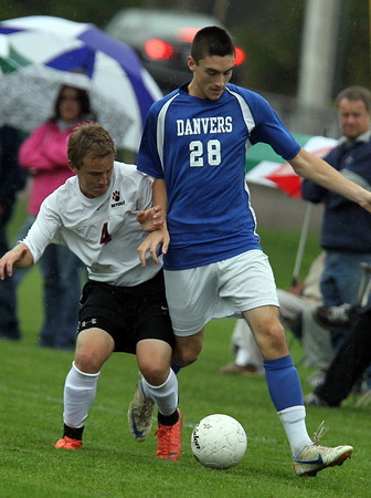 Beverly's Jack Atherton, left, challenges, Danvers' Drew Piazza, right, for the ball on a rainy Tuesday afternoon. David Le/Staff Photo