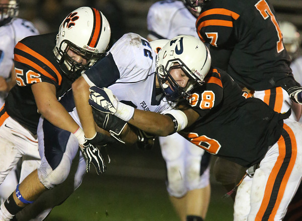 Peabody's Tanner Moquin gets taken down by two Beverly defenders on Friday night at Hurd Stadium in Beverly. David Le/Staff Photo