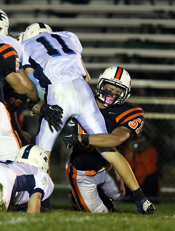 Beverly senior linebacker Rob Cattell, right, wraps up Peabody quarterback Michael Raymond on a sweep play. The Panthers dominated all night and came away with a 49-0 win over the Tanners. David Le/Staff Photo