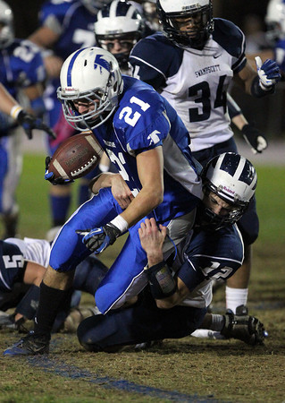 Danvers running back Alex Valles, left, gets taken down by Swampscott defensive back Brian Santry, right, after a big gain. Valles rushed for 162 yards and two scores to lead the Falcons to a 35-7 victory over the Big Blue on senior night.  David Le/Staff Photo