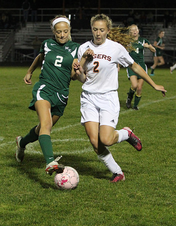 Manchester-Essex's Sarah Lewiecki, left, and Ipswich's Emily Evans, right, collide while battling for a loose ball on Tuesday evening. David Le/Staff Photo