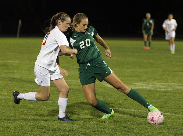Manchester-Essex junior captain Rachel Daley, right, shields the ball from Ipswich sophomore Maggie Marsh, left, on Tuesday evening. David Le/Staff Photo