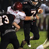 Marblehead senior quarterback Ian Maag stiff arms Gloucester's Devin Hemeon, and looks for running room against the Fishermen on Friday evening at Piper Field in Marblehead. David Le/Staff Photo