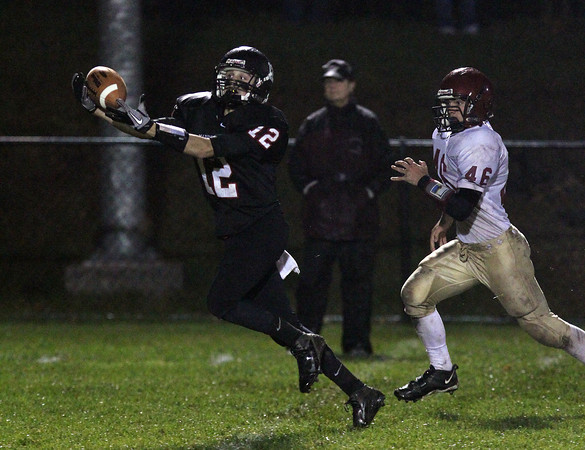 Marblehead wide receiver Brian Daly, left, stretches out to haul in a long pass from quarterback Ian Maag after beating Gloucester defensive back Alex Enes, right, and runs the distance for a Magicians score. David Le/Staff Photo