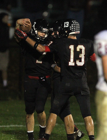 Marblehead's Ian Maag, left, celebrates with his teammates after scoring a rushing touchdown against Gloucester. Maag ran for a touchdown and passed for 234 yards and 5 scores and Marblehead defeated Gloucester 39-12 on Friday evening. David Le/Staff Photo