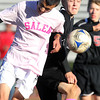 Salem High School's Jason Alas, left, wins a header from Marblehead's Paul Elder, right, on Friday afternoon. Both Salem and Marblehead sported pink attire in recognition of Breast Cancer Awareness Month. David Le/Staff Photo