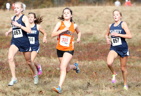 From left, Peabody senior Heather McLean, Beverly junior Nicole Demars, and Peabody sophomore Lauren Barrett run in a tight pack as they cross the one mile mark during the NEC Cross Country Championship at Bradley Palmer State Park in Hamilton on Saturday afternoon. David Le/Staff Photo