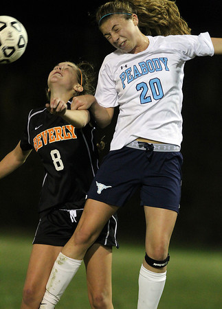 Peabody's Madison Doherty, right, and Beverly's Allison Collins, left, get tangled up as they battle for a header on Friday night.  David Le/Staff Photo