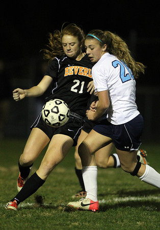 Beverly's Rosre Terner, left, plays the ball upfield while being pursued by Peabody's Madison Doherty, right, on Friday evening.  David Le/Staff Photo