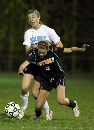 Peabody's Madison Doherty collides with Beverly's Allison Collins as they battle for control of the ball on Friday night.  David Le/Staff Photo