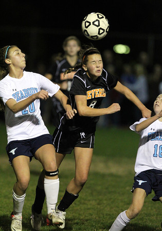 Beverly's Allison Collins, center, leaps in between Peabody's Madison Doherty, left, and Caroline Colbert, right, to win a header on Friday night.  David Le/Staff Photo