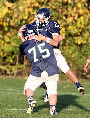 Pingree senior quarterback Jerome Cappadona jumps into the arms of teammate Henry Martin after Cappadona completed a long touchdown pass to junior John Spears against Holderness on Saturday afternoon. David Le/Staff Photo