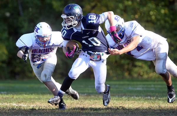 Pingree sophomore Salvatore Fazio breaks the tackle of two Holderness defenders on Saturday afternoon. David Le/Staff Photo