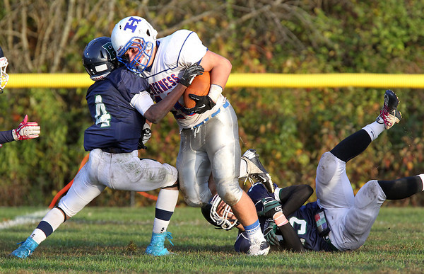 Pingree junior John Spears, left, and freshman Justin Assad, right, take down Holderness sophomore Jake Rourke, during the 4th quarter of play. Holderness scored a late touchdown and converted a 2-point conversion to defeat Pingree 35-34. David Le/Staff Photo