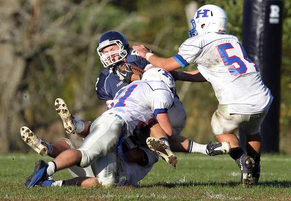 Pingree junior tight end Kyle Lentini, center, holds onto the football while being tackled by a gang of Holderness defenders on Saturday afternoon. David Le/Staff Photo