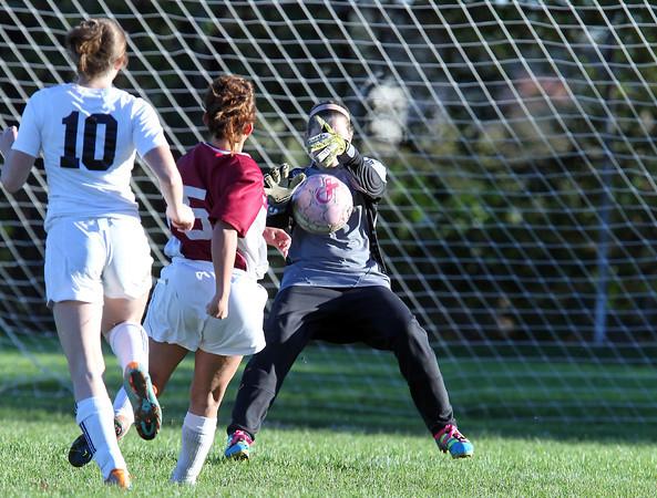 Salem High School goalkeeper Ariana Gaffney, right, makes a point blank save on Lynn English forward Abbie Martocchio, center, as Salem's Hayley Jellison, left, looks on. David Le/Staff Photo