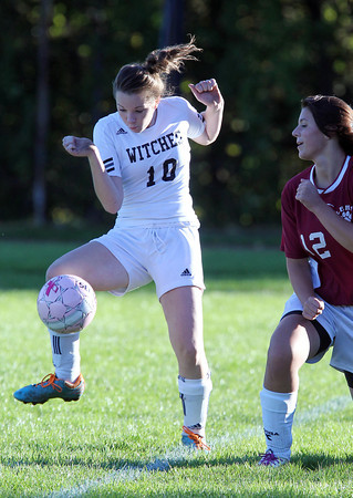Salem High School defense Hayley Jellison, left, controls the ball while Lynn English's Brianna Goulet, right, looks on. David Le/Staff Photo