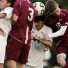 St. John's Prep junior striker Matthew Chilton, center, wins a head ball in between BC High senior Neil Flanagan, left, and senior Madison Barnwell, right, during the second half of play on Wednesday afternoon. David Le/Staff Photo