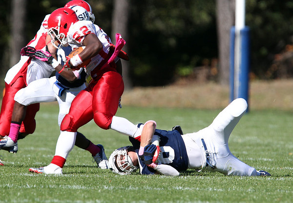St. John's Prep senior Conor Powers, right, grabs ahold of St. John's Shrewsbury running back Shadrach Abrokwah, left, and brings him down for a loss on Saturday afternoon. David Le/Staff Photo