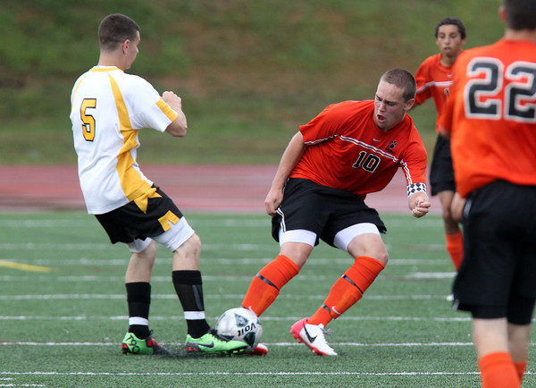 Beverly senior captain Cam Rogers, right, goes in hard to challenge Bishop Fenwick senior Giorgio DiCostanzo, for a loose ball on Tuesday afternoon. David Le/Staff Photo