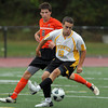 Bishop Fenwick senior captain Drew Thibodeau steps over the ball while being pursued by Beverly's Nate McGlaughlin on Tuesday afternoon. David Le/Staff Photo