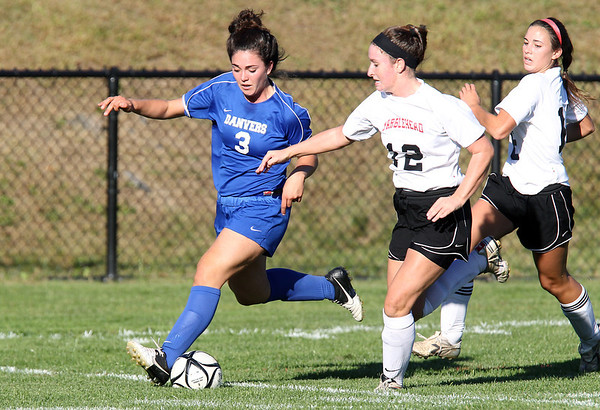 Danvers junior Kylie Plaza, left, carries the ball upfield while being pursued by Marblehead senior Meggie Collins, right, on Thursday afternoon. David Le/Staff Photo