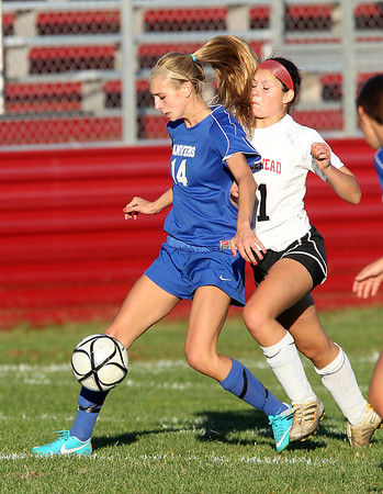 Danvers sophomore Emily Murphy, left, tries to keep possession of the ball while being run into by Marblehead's Monica Thorne, during the second half of Thursday afternoons game between the Falcons and Magicians. David Le/Staff Photo