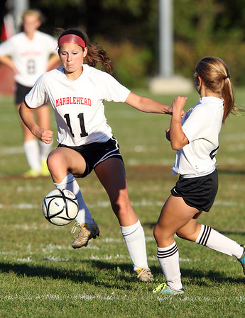 Marblehead junior Monica Thorne, left, takes possession of the ball next to teammate Sarah Cullen, right, against Danvers on Thursday afternoon. David Le/Staff Photo