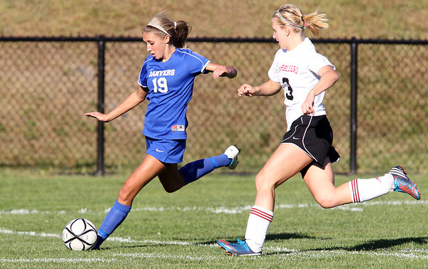 Danvers junior Delaney Zecha, left, crosses the ball into the box while being chased down by Marblehead sophomore Audrey Meakin, right, on Thursday afternoon. David Le/Staff Photo