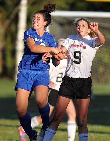 Danvers junior Kylie Plaza, left, and Marblehead sophomore Mia Bongiorno, right, battle midair to win a header during the second half of play on Thursday afternoon. David Le/Staff Photo