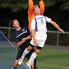 Danvers senior captain Brian Trefry, right, leaps high in the air as Swampscott goalie Val Temin makes a save while Swampscott defender Ray Rosa, left, looks on. David Le/Staff Photo