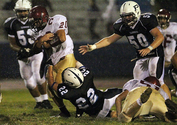 Peabody's Tanner Moquin, center, tries to wrap up Gloucester ball carrier Mark Horgan, left, while Tanner teammate Frankie Lowry, right, closes in. David Le/Staff Photo