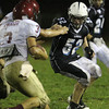 Peabody senior Brian Norwood, right, tries to bring down Gloucester ball carrier Santo Parisi on Friday night. David Le/Staff Photo