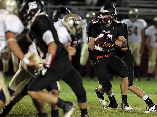 Marblehead sophomore running back Brooks Tyrrell, right, looks for running room against Winthrop on Friday evening. David Le/Staff Photo