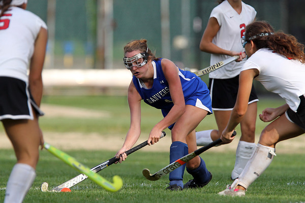 Danvers' Sarah Potter, center, strikes the ball upfield while being pursued by a few Marblehead defenders. David Le/Staff Photo