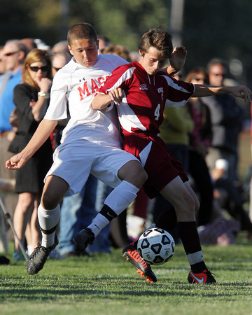 Masco junior Jack Heintzelman, left, and Newburyport senior Connor Glynn, right, get tangled up as they fight for possession of the ball on Tuesday afternoon. David Le/Staff Photo
