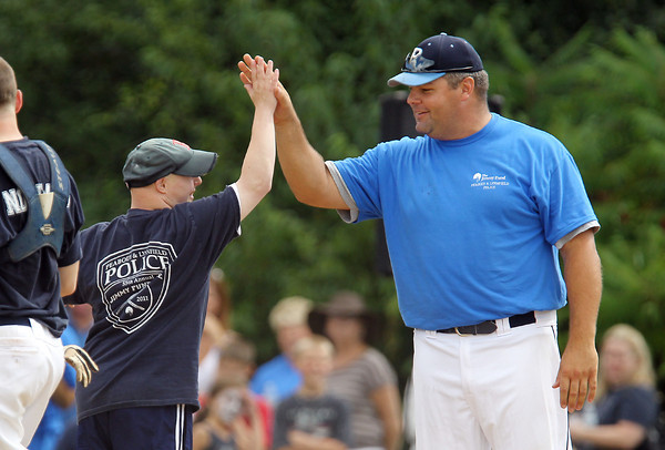 Peabody policeman Mark Bettencourt, right, gives a high-five to pinch hitter Mike Zaccarini, left, after he crossed home plate with a pinch hit home run. David Le/Staff Photo