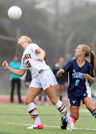 Beverly midfielder Eva Gourdeau, left, wins a header while being pursued by Peabody midfielder Christa Trombley on Saturday morning. David Le/Staff Photo