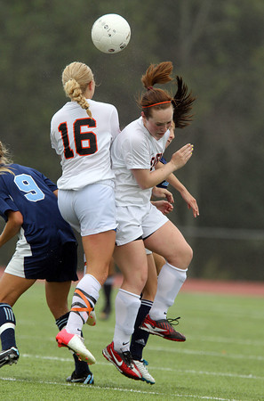 Beverly's Sarah Visnick, right, Eva Gourdeau, left, collide with a couple Peabody players as they go up to win a head ball during the first half of play on Saturday morning. David Le/Staff Photo