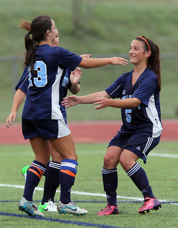 Peabody senior forward Victoria Digiacomo, left, gets a hug from teammate Katrina Silva, right after Digiacomo scored on a penalty kick to put the Tanners up 1-0 over Beverly. The one goal lead was enough to propel the reigning State Champs to a victory on a drizzly Saturday morning. David Le/Staff Photo