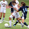 Beverly junior midfielder Caitlin Harty tries to keep control of the ball while Peabody senior defense Kara Digiacomo challenges for possession. David Le/Staff Photo